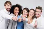 Enthusiastic group of people giving a thumbs up — Stock Photo