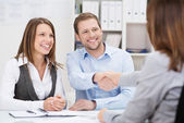 Smiling young man shaking hands with an agent — Stock Photo