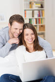 Young couple grinning at content on the laptop — Stock Photo