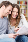 Young couple laughing as they discuss paperwork — Stock Photo