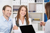 Smiling couple chatting to a business broker — Stock Photo