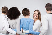 Group of friends linking arms facing away — Stock Photo