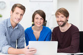 Confident business team grouped around a laptop — Stock Photo