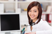 Smiling young woman with a headset around her neck — Stock Photo