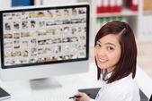 Young Asian woman editing photographs — Stock Photo
