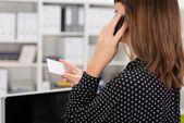 Woman phoning a business off details on a card — Stock Photo