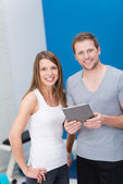 Young couple at the gym monitoring their exercise — Stock Photo