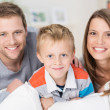 Happy little boy with his smiling young parents — Stock Photo