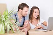 Paar umzug schaut auf einen laptop — Stockfoto