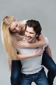 Playful couple riding piggy back together — Stock Photo