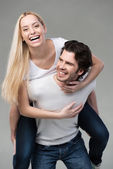 Young couple having fun riding piggy back — Stock Photo