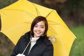 Attractive smiling woman under a yellow umbrella — Stock Photo