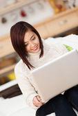 Mladá asijská žena pracující na přenosném počítači — Stock fotografie