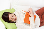 Exhausted student sleeping with her text book — Stock Photo
