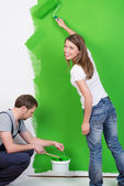 Young couple painting their new home green — Stock Photo