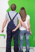 Mladý pár, obdivoval nově natřené zdi — Stock fotografie