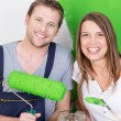 Happy excited couple painting their new home — Stock Photo #44140503