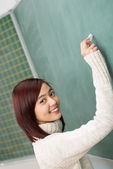 Friendly student or teacher writing on a board — Stock Photo