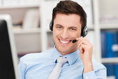 Handsome businessman using a headset — Stock Photo