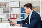 Hardworking young businessman at his desk — Stock Photo