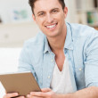 Handsome friendly young man holding a tablet — Stock Photo