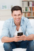 Young man holding his mobile as he relaxes at home — Stock Photo