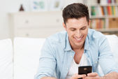 Man smiling ad he reads a message on his mobile — Stock Photo