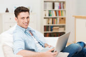 Young man relaxing at home with a laptop — ストック写真