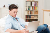 Young man concentrating as he works on a laptop — Stock Photo