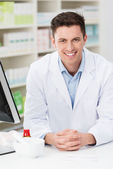 Handsome friendly young pharmacist — Stock Photo
