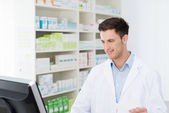 Smiling pharmacist checking stock on his computer — Stock Photo