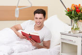 Friendly young man reading in a hospital bed — Stock Photo