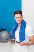 Young man standing in a gym with a clipboard — ストック写真