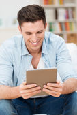 Handsome man reading on his tablet computer — Stock Photo