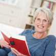 Smiling friendly senior woman reading a book — Foto Stock #45283727