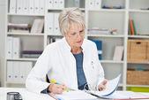Elderly businesswoman working at her desk — Stock Photo