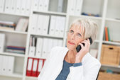 Elderly businesswoman listening to a call — Stock Photo