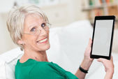 Attractive senior woman using a tablet computer — Stock Photo