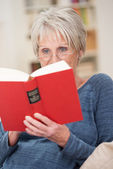 Senior woman relaxing with a book — Stock Photo