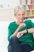 Beautiful elderly woman checking the time — Stock Photo