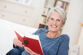 Smiling friendly senior woman reading a book — Stock Photo