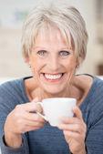 Mujer senior pelo corto rubia sostiene una taza — Foto de Stock