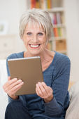 Caucasian modern senior woman holding a tablet PC — Stock Photo