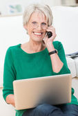 Delighted elderly woman chatting on a mobile — Stock Photo