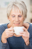 Attractive senior woman savoring a cup of coffee — Stock Photo