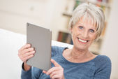 Happy senior woman holding a tablet — Stock Photo