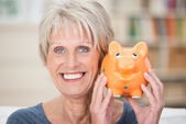 Excited senior woman holding up her piggy bank — Stock Photo