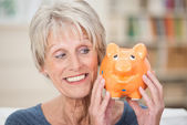 Charismatic elderly woman holding up a piggy bank — Stock Photo