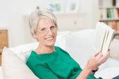 Relaxed happy senior woman enjoying a book — Stock Photo