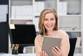 Smiling businesswoman holding a tablet — Stock Photo